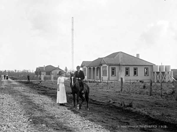 Awanui Radio VLA in 1919. The Officer-in-Charge's house (left) and Officers' Quarters, with the station visible in the distance. A woman with a boy on horseback stand in Wireless Road in the foreground.