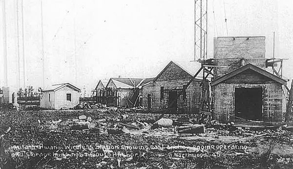 An excellent overall view of Awanui wireless station c1912. Anchor blocks for the tower can be see at the far left and far right (the eastern block, under construction). Other buildings (L-R) are storeroom, operating house and engine house