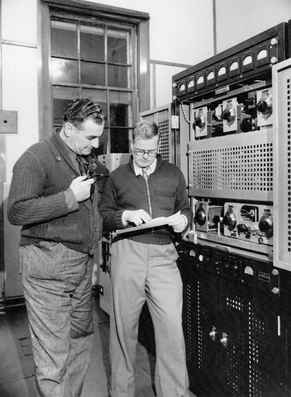 In the transmitter building at Awarua Radio ZLB, c1946. Ernie Hancock on the right.