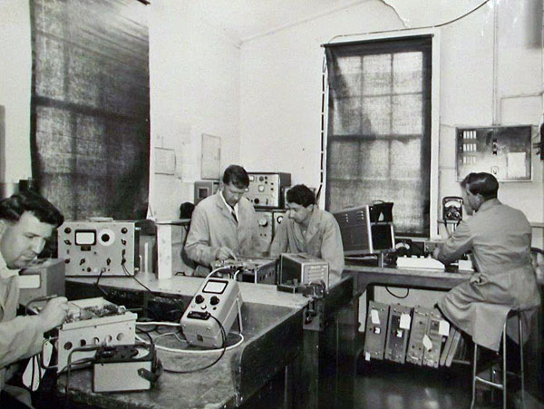 Workshop at Awarua Radio Depot: L-R: E Plimley (on loan from Auckland) tests a radiotelephone transmitter, J Piper (Senior Technician) and I Gow tune a radio receiver, B Lynn tests a section of the radiotelephone set which will be installed on Bluff Hill for communication with Halfmoon Bay