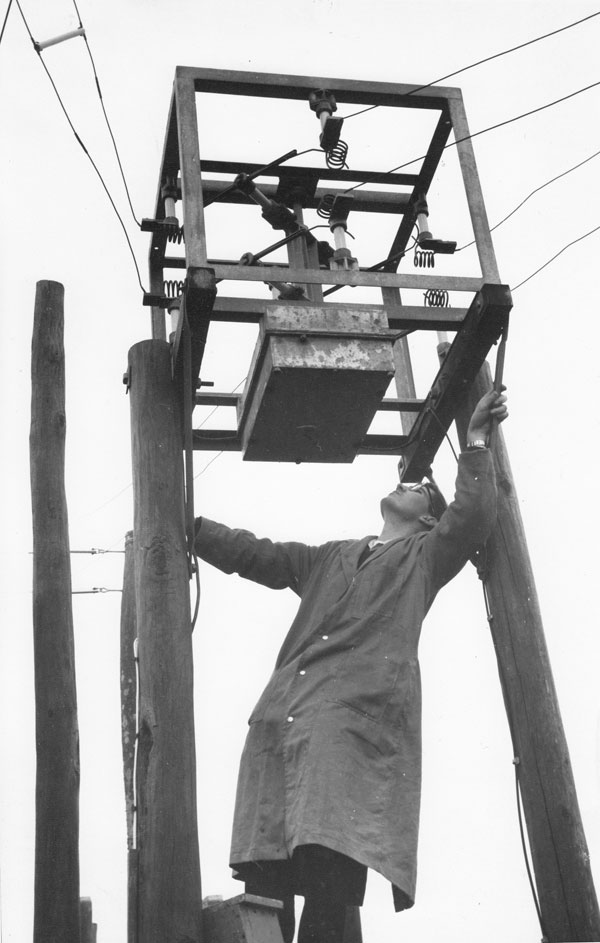 Technician inspects power-driven aerial transmission line switch, one of many such switches controlled from a console in the transmitter hall