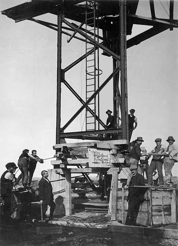 "It appears workers are jacking up the tower in order to remove the timbers, on which the tower was built, before lowering the tower onto its glass insulators. The sign appears to read: ""Viewers (Visitors?) are not allowed on the tower. By order""."