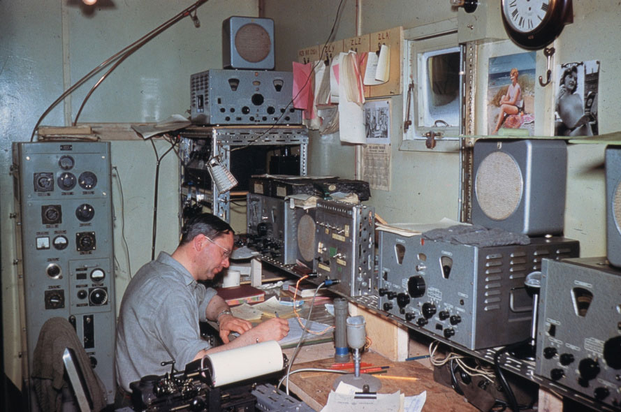 Scott Base radio room 1959-1960. Some interesting details in this photo: the operator's mittens drying out on top of the receiver, the clipboards on the wall for stations ZLY, ZLZ and ZLA, and the pin-up photos. Well it was 1959 after all.