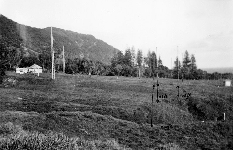 Raoul Island Radio, April 1950: 'Looking west, showing whole aerial system and east gully.' The three measurements on the photo look to be horizontal distances between gully and various poles