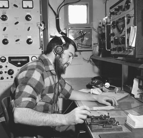 Radio operator with Racal transmitter and receivers, Scott Base, 1965-1966