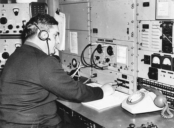 Make a telephone call to Milford Sound and it goes via Awarua Radio. Cyril Burke, a telephonist at Awarua, checks this circuit.