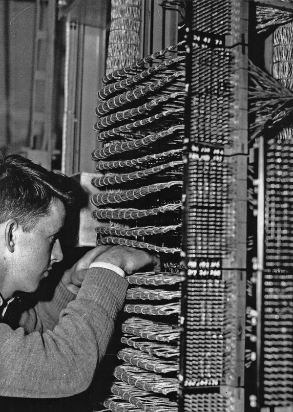 Pat Connor checking wiring of the main patch panel in the Carrier Room at Himatangi Radio, c1950s
