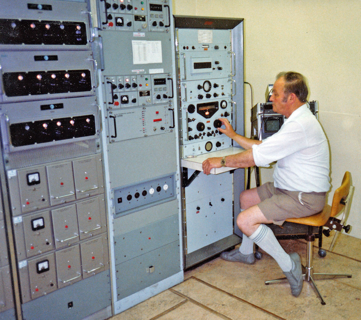 By the late 1980s an additional rack of Harris Exciter units had been installed and the Racal receiver was repositioned. Don Nichol is shown at the receiver, c1980s