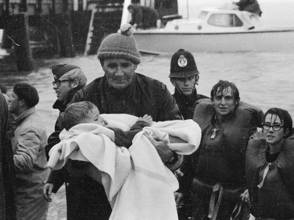 Policeman Ray Ruane carries a young survivor of the Wahine disaster. At right, Gregory Mackenzie and Diane Parnell, students at University of Otago.