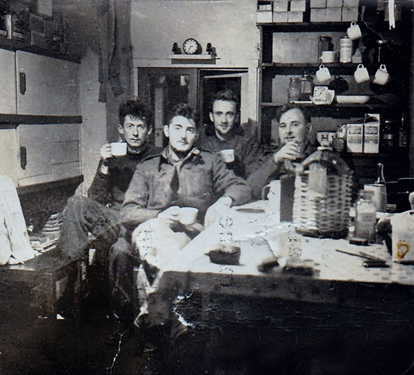 In the kitchen at Campbell Island, 1951. HJ 'Bert' McKechnie in front.