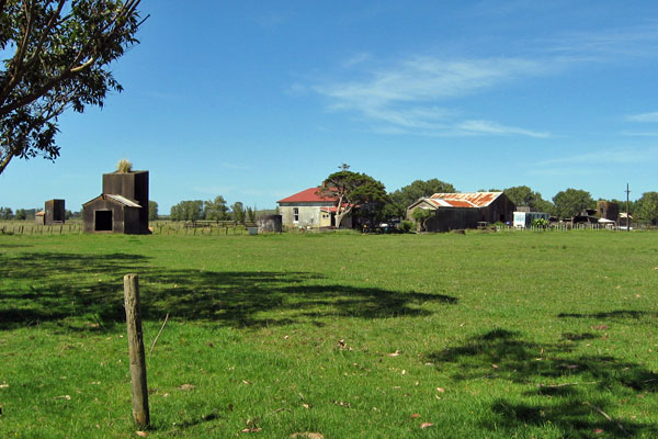 Remains of the original Awanui Radio, looking northeast and showing the operating building in the centre, with the smaller storage building to the right and the engine house in the distance. All three anchor blocks for the tower guys can also be seen.