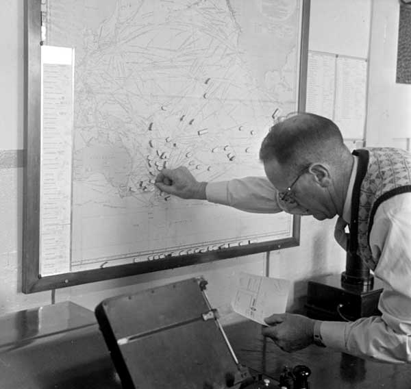 Wellington Radio Supervisor Austin Sumner places magnets representing ships on a map of the South Pacific in 1957