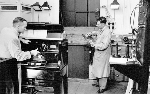 George Bourne (left, working on a Muirhead-Jarvis facsimile machine) and N Holding at the Radiotelegraph and Cables Terminal