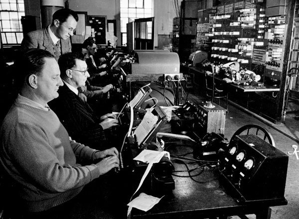Photo labelled 'Internal Telegraph Office: Press Teleprinter transmitting position; line control and relay circuits in the right background.'
