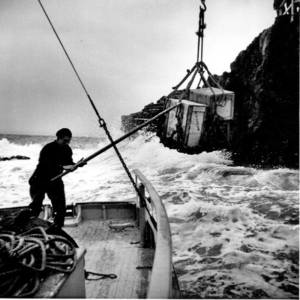 """Two crates, one of them labelled """"Made in England"""" being unloaded at Stephens Island"""