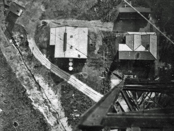 Looking down from the top of the 400' mast at Awarua Radio. The transmitter building is at the right of the photo, and one of the three concrete anchor blocks for the tower is at the top left of the photo