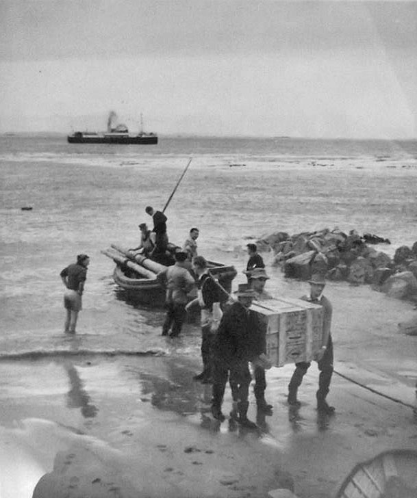 Lighthouse keepers and NZPO staff bring materials for radio installation ashore at Dog island in the 1950s