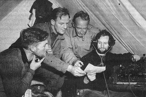 In the ZLKC Radio tent at Stillwater River Base Camp, L-R: Bob Miller (survey leader), Buster McKane (field leader), John Howard (US Army), Frank Barlow (Radio Operator)