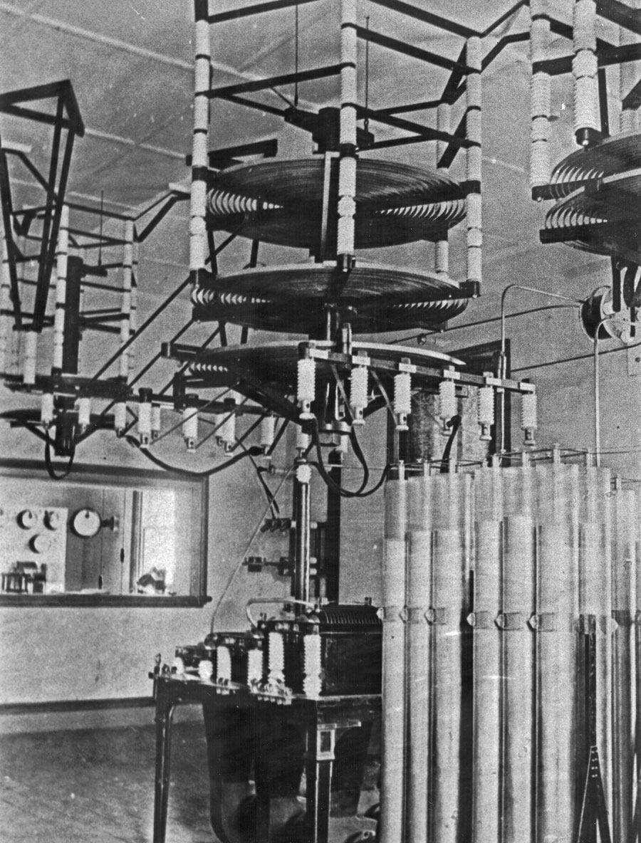 Leyden jars in foreground and tuning coils hanging from the ceiling. Through the window can be seen a portion of the switchboard in the operating room. The aerial switch is in the corner of the room, partially obscured by the tuning coils.