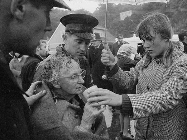 A Wahine survivor receives soup after landing on Seatoun beach, 10 Apr 1968. Salvation Army Capt David Bennett is at far left.